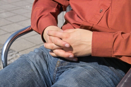 clasped hands man sitting in jeans
